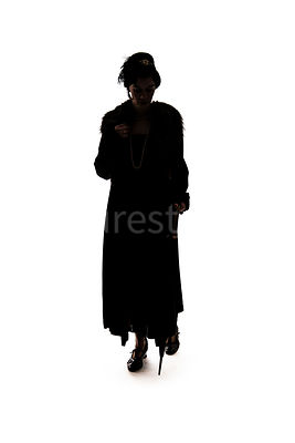 A silhouette of a vintage early 1900s to 1930s woman in a long coat – shot from eye level.