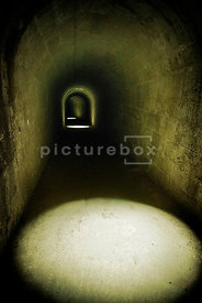 An atmospheric image of sunlight pouring down into a dark underground tunnel through some light wells.