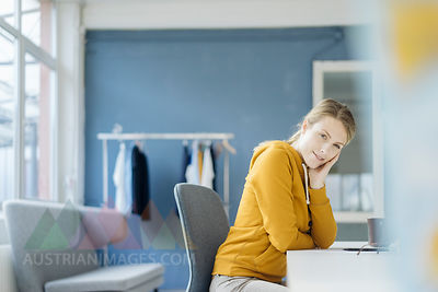 Portrait of fashion designer sitting at desk in her studio