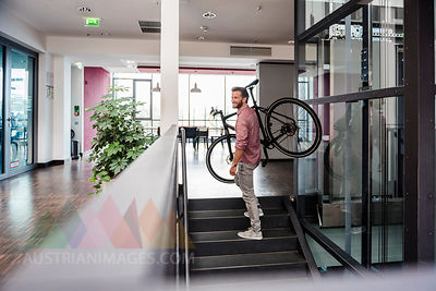 Man with bicycle walking upstairs in modern office