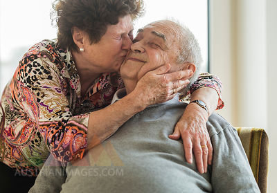 Senior woman hugging and kissing his husband