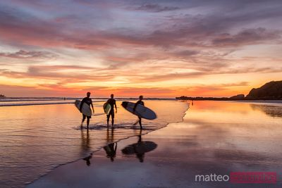 Surfers at sunset walking on beach, Playa Guiones, Costa Rica