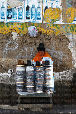 Aymara woman selling bowler hats in front of abobe wall and beer posters, La Paz, Bolivia