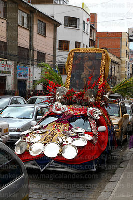 Decorated car with painting of Jesus Christ on roof driving through street on Good Friday, La Paz, Bolivia