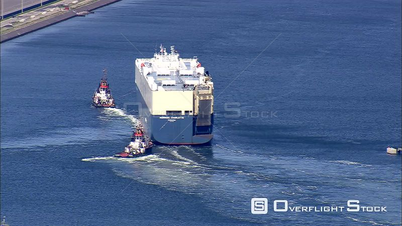A pair of tugboats guiding the car carrier Morning Charlotte along a harbor channel