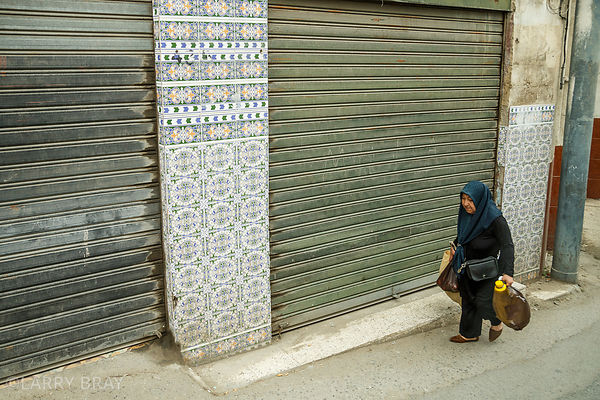 Lady with shopping walking past tiled walls in Algiers, Algeria, North Africa