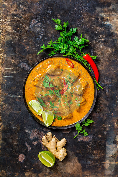 Traditional curry and ingredients on dark background. Curry, lime, ginger, chili, naan bread, rice, couscous, herbs and spice...