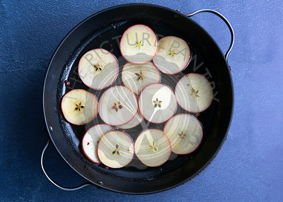 Uncooked sliced apple in a pan of honey, sugar and water.
