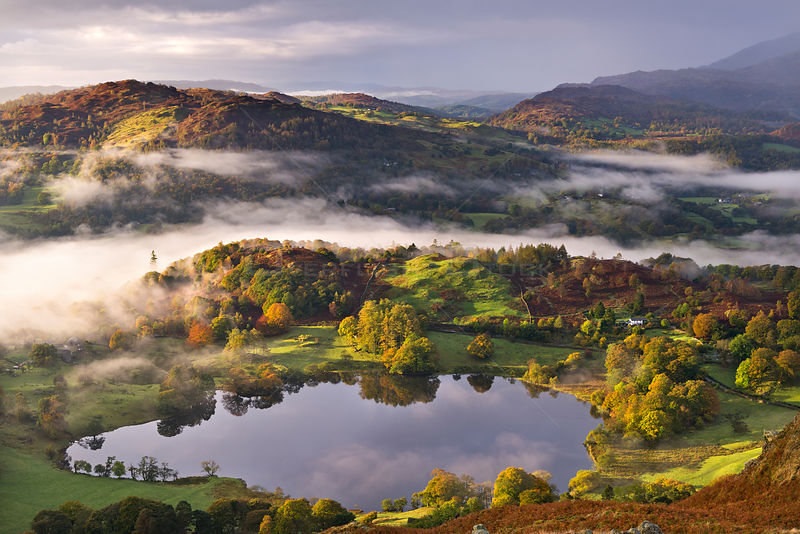 Loughrigg Tarn surrounded by misty autumnal countryside, Lake District National Park, Cumbria, England. October 2012. Highly ...