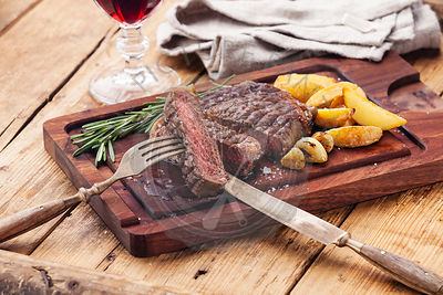 Medium rare grilled Beef steak Ribeye with roasted potato wedges on cutting board on dark wooden background