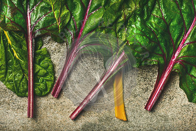 Flat-lay of fresh leaves of swiss chard over concrete stone background, top view, horizontal composition