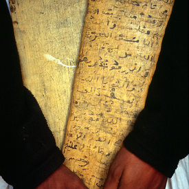 A librarian in Chingetti, Mauritania, 'lah' or wooden tablet on which is inscribed verses of the Koran