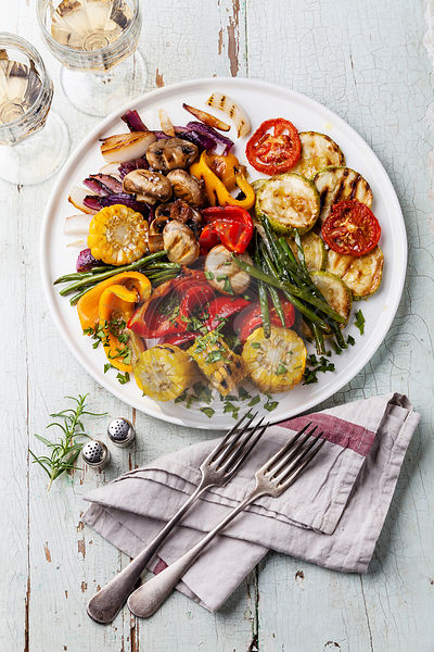 Grilled vegetables on the white plate on blue textured background