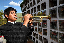 Trumpeter playing for souls of the deceased in cemetery during Todos Santos festival, La Paz, Bolivia