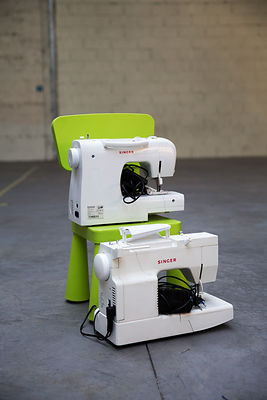 Deux machines à coudre sur une chaise en plastique dans un hangar, Lyon, France / Two sewing machines on a plastic chair in a...