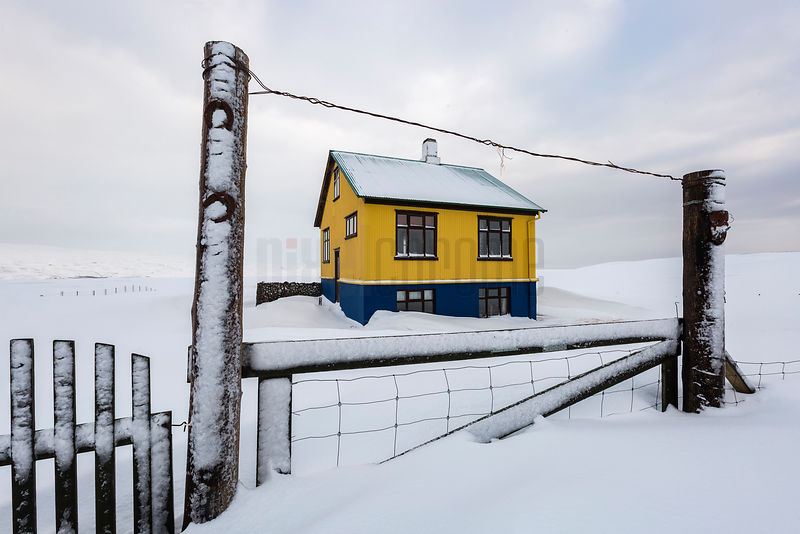 Yellow House in the Middle of a Snow Covered Landscape