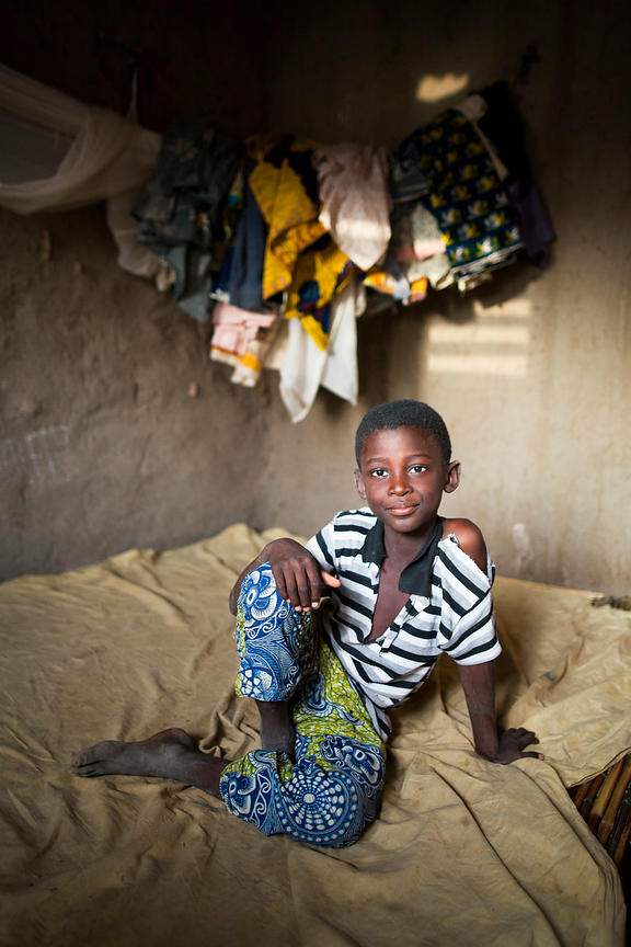 Mohamadi assis sur son lit de paille dans sa chambre, Ponsom Tenga, Burkina Faso / Mohamadi sitting on his straw bed in his r...