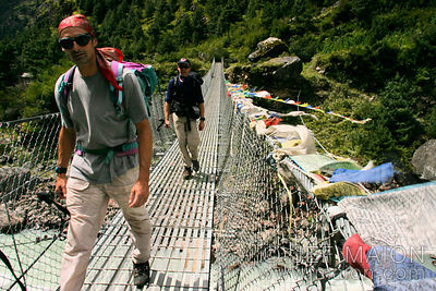 Trekkers cross a suspended bridge