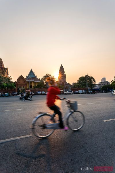 Woman riding a bicyle at sunset, Phnom Penh, Cambodia