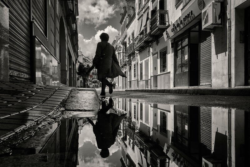 Reflection in a Puddle of a Woman Crossing a Road in Triana