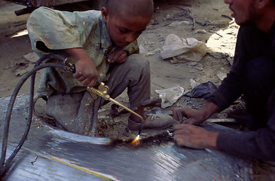A child welding an engine frame, Mazar-i-Shariff, Afghanistan