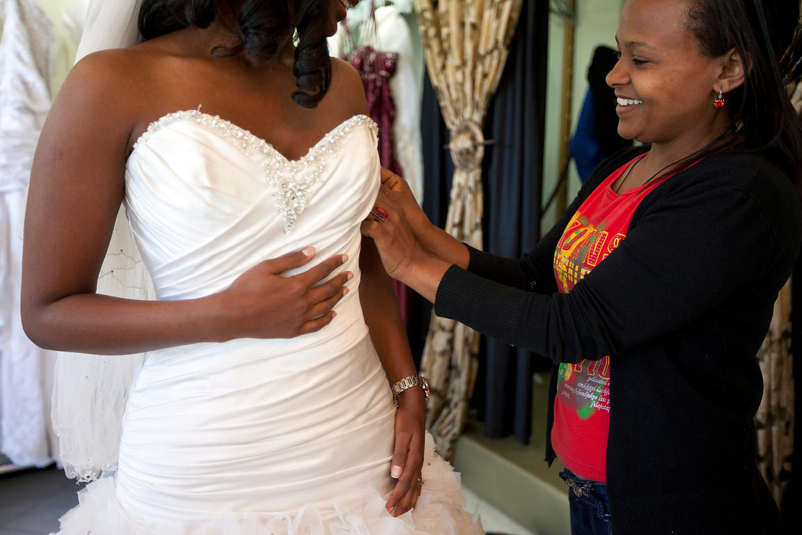 Ethiopia - Addis Ababa - A portrait of a woman that works in a wedding dress shop in a new mall helping a customer in her dress