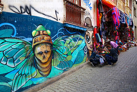 Street art and tourists browsing textiles hanging outside shop in tourist market, La Paz, Bolivia