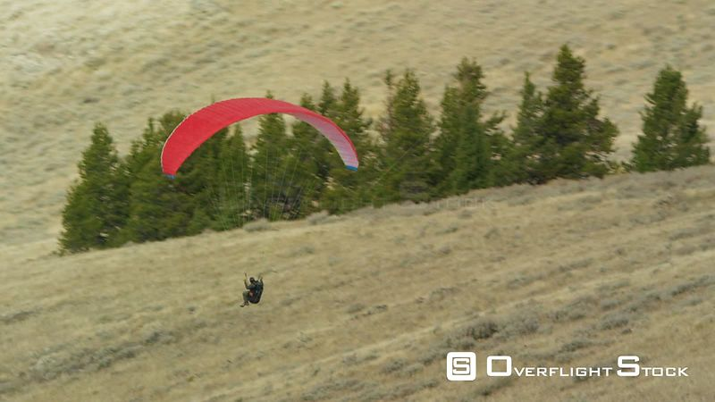 A paraglider soars above a sagebrush covered hilltop near Yellowstone National Park and West Yellowstone, Montana