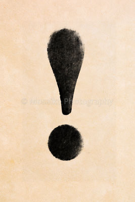 Old black, frayed grunge exclamation icon on brown paper