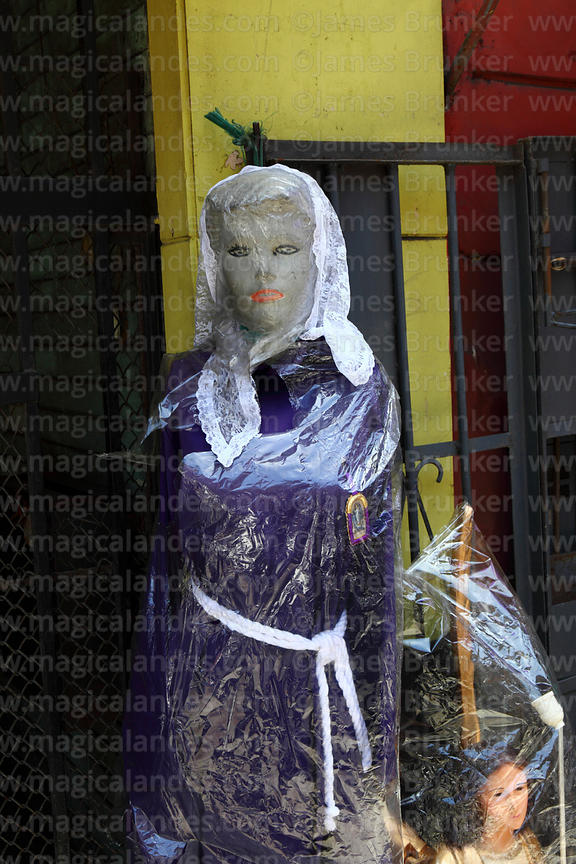 Mannequin wearing purple robes worn by devotees of Señor de los Milagros outside shop, Lima, Peru