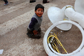 Boy playing with sousaphone left on ground, Virgen de la Candelaria festival, Puno, Peru