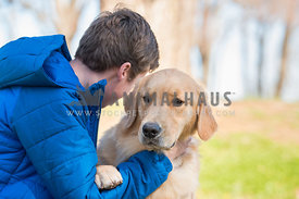 yellow lab being hugged by teenage boy in coat
