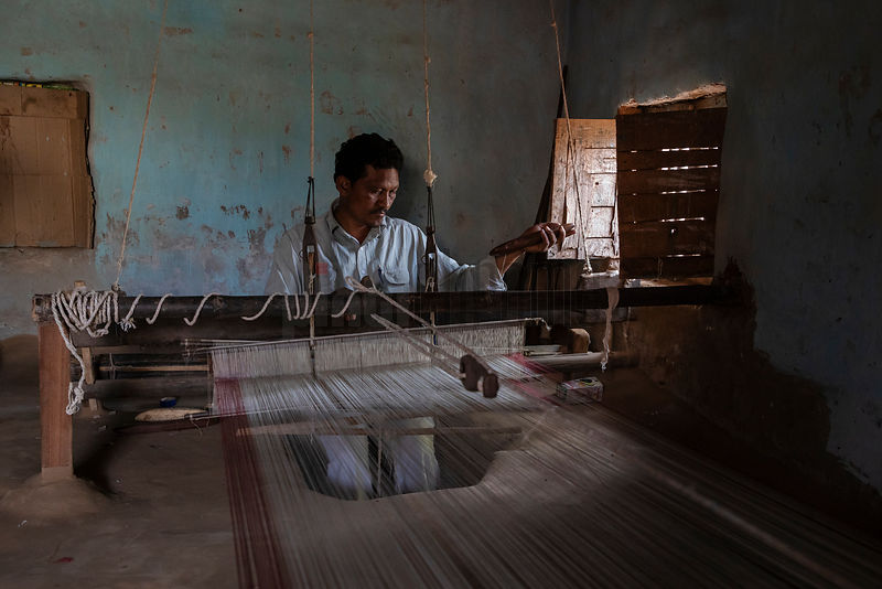 Portrait of a Weaver using a Pit Loom to Weave Traditional Fabrics