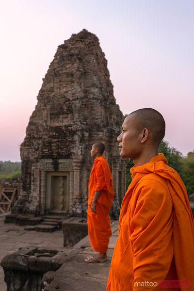 Two buddhist monks looking at sunset, Angkor, Cambodia