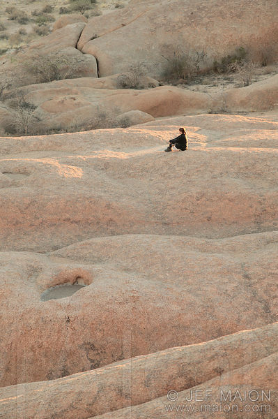 Woman sitting on rock formations