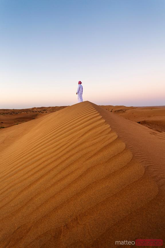 Oman, Wahiba Sands desert. Man with arab dress at sunrise