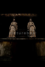 An atmospheric image of some statues in a dark temple.
