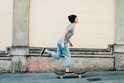 Young female skate boarder driving with her skateboard