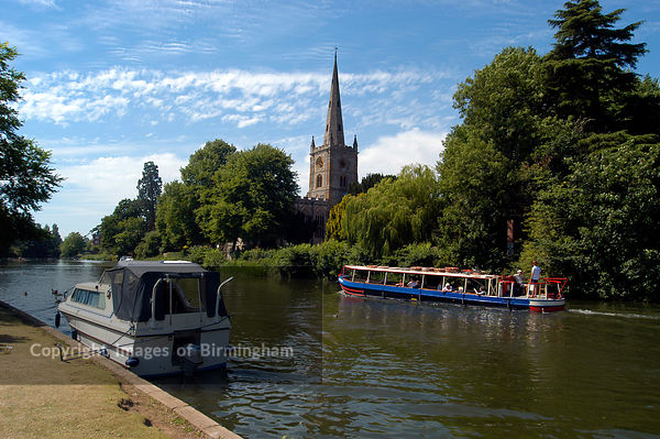 Boats at Stratford upon Avon, Warwickshire. Swans and riverboats, river Avon. Canal boat for tourists and church.