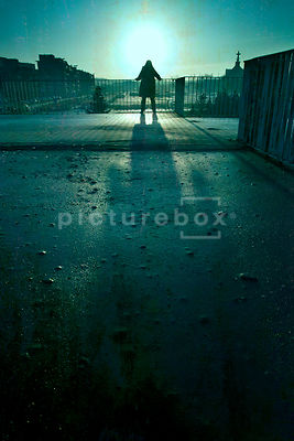 An atmospheric image of the silhouette of a mystery woman, standing and looking over a railing towards the city car park of a...