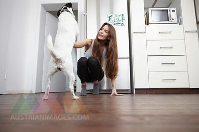 Young woman in kitchen playing with dog
