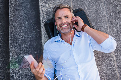 Smiling man lying on stairs with cell phone and earbuds