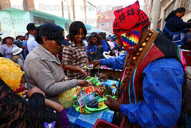 Aymara shaman blessing miniature house with alcohol at Alasitas festival, Puno, Peru