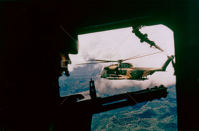 VIETNAM -- 1960s -- A door gunner looks out over the rainforest of South Vietnam from an HH-53 helicopter of the 40th Aerospa...