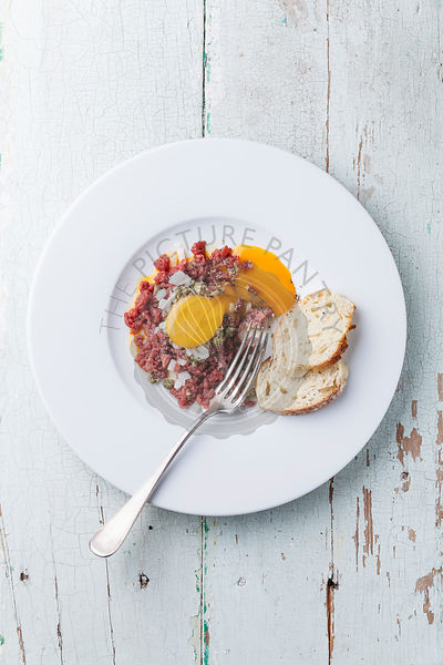 Beef tartare with capers and onion on white plate on blue background