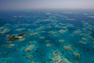 Aerial view of small sand and coral cayes and coral bommies inside southern Belize barrier reef in vicinity. Near Placencia, ...