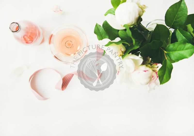Rose wine, decorative ribbon and peony flowers over white table