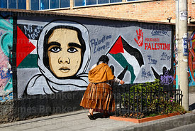 Aymara woman or cholita walking past a mural showing support for Palestine, La Paz, Bolivia