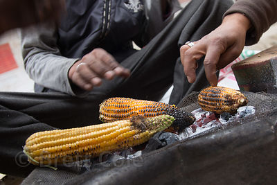 Vendors sell baked corn at a market in Leh, Ladakh, India