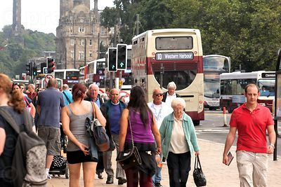 Bustle of Shoppers in Princes Street whilst a Line of buses Pass by